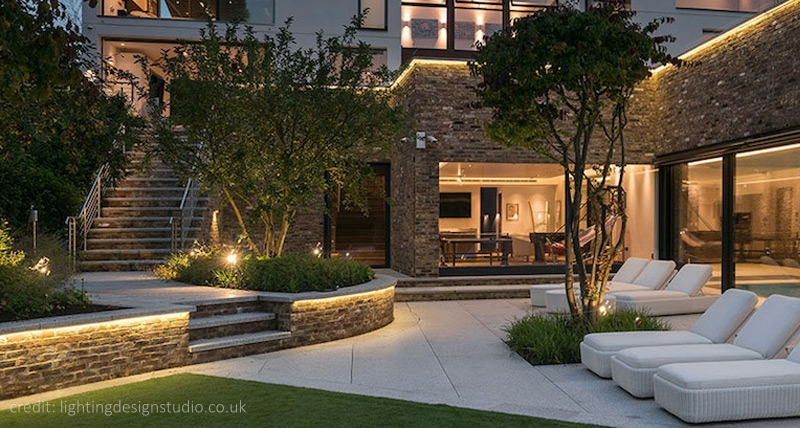Landscape lighting with a large house and garden backdrop